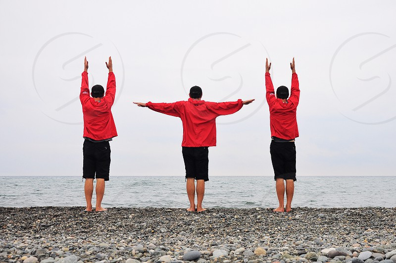 3 people wearing red jackets standing on beach near body of water photo