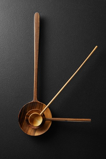 close-up view of a wooden spoons with clock hands photo