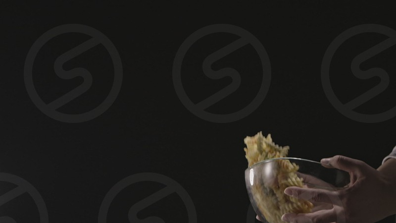 Flying and falling raw homemade italian pasta Fusilli Spirale from glass bowl on a black background. Slow motion Full HD video 240fps 1080p. photo