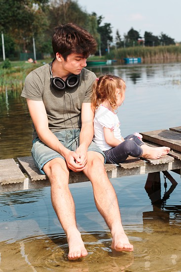 Young boy and his little sister sitting on jetty over the lake and dipping feet in water on sunny day in the summertime photo