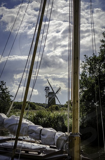 A windmill in the background is beautifully framed by the mast & rigging of the sailboat in the foreground photo