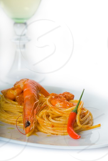 italian spaghetti pasta and fresh spicy shrimps saucewith a grass of dry white wine on background photo