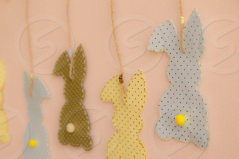 Rabbit shaped cloth patches hanging on the wall. photo