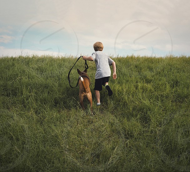 A boy runs up the side of a grassy hill with his pet dog.  photo