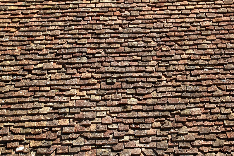 square roof tiles plain clay pattern weathered aged Pyrenees architecture detail photo