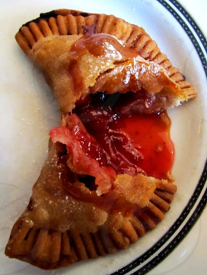 Split fried strawberry pie on white plate with black border photo