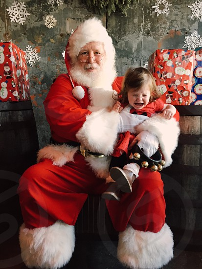 man in santa claus costume carrying girl crying photo