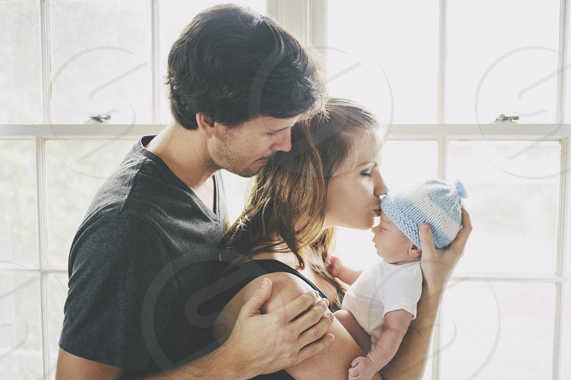 man standing behind a woman carrying a newborn by a clear glass window photo