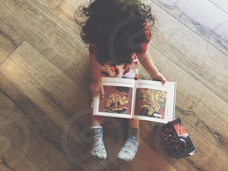 girl wearing red floral shirt holding book sitting on brown wooden surface photo