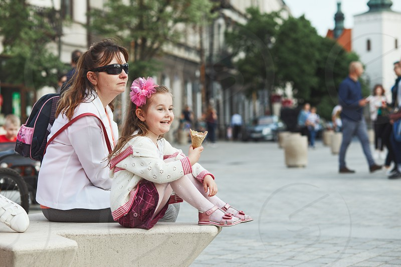 Mother and daughter spending time together sitting in the center of town little smiling girl holding and eating ice cream. Candid people real moments authentic situations photo