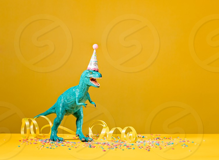 Toy dinosaur with birthday party hat on a yellow background. photo
