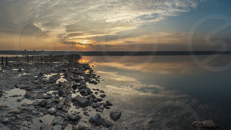 The shore of a drying lake in the rays of a colorful sunset photo