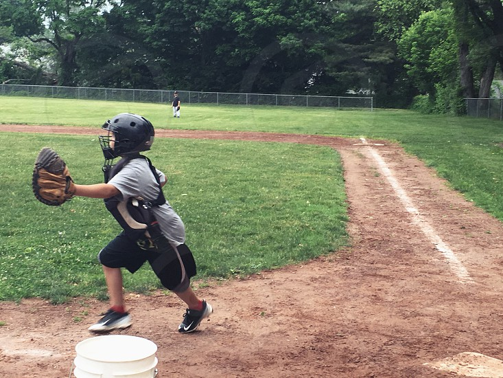 children on gray and black baseball suit running about to catch the ball near the plastic pail on the baseball field during daytime photo