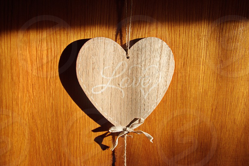 Wooden heart shape with text Love hanging on the wooden background photo