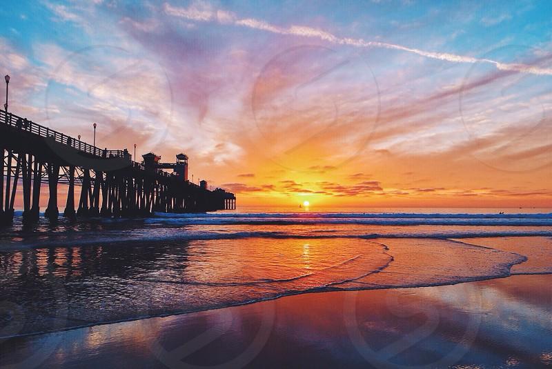 ocean sunset near wooden pier photo