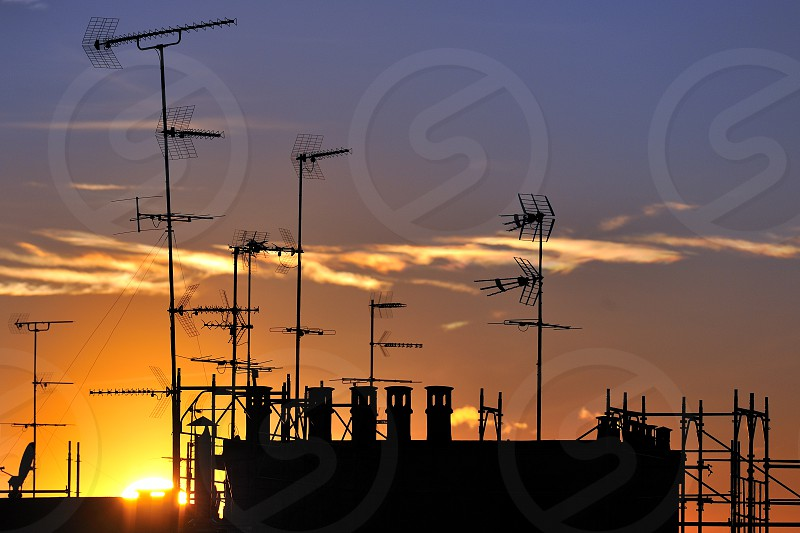 Sunset over antennas and roofs Milano Italy photo
