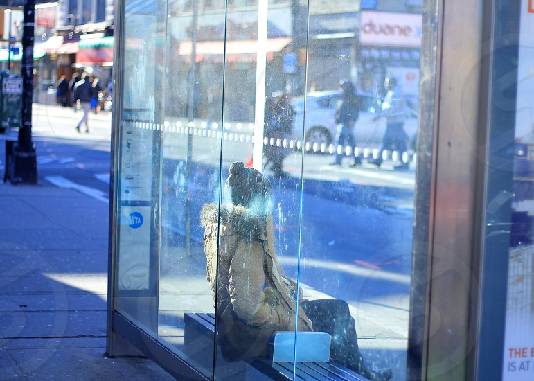 person wearing tan coat sitting at glass window bus stop photo