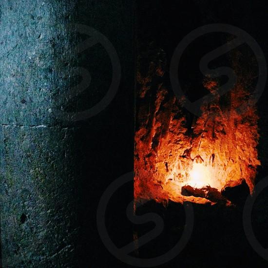 Candle behind stone pillar photo