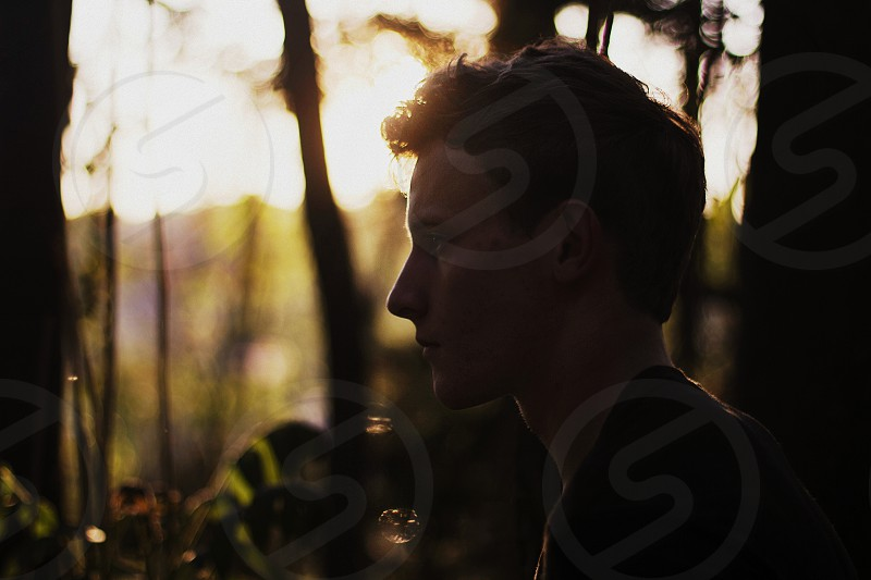 Inspirational nature young man portrait silhouette film light sun flare sunset photo