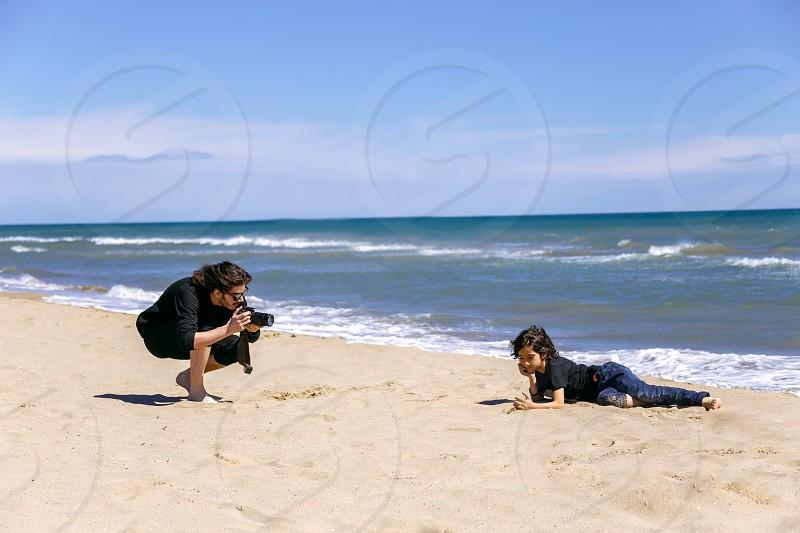 Professional photographer with photo camera shooting teenage boy lying on sandy beach of ocean coast photo