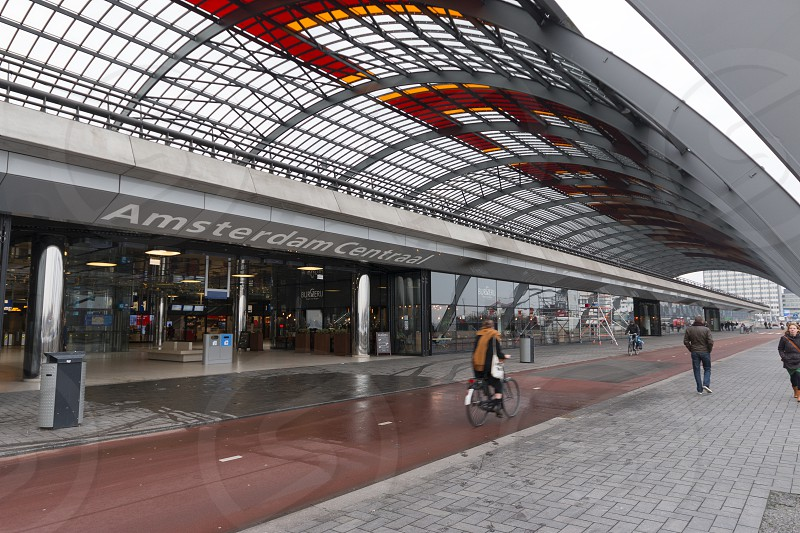 Amsterdam Centraal station - Amsterdam Main Entrance on the North Side with cyclist. photo