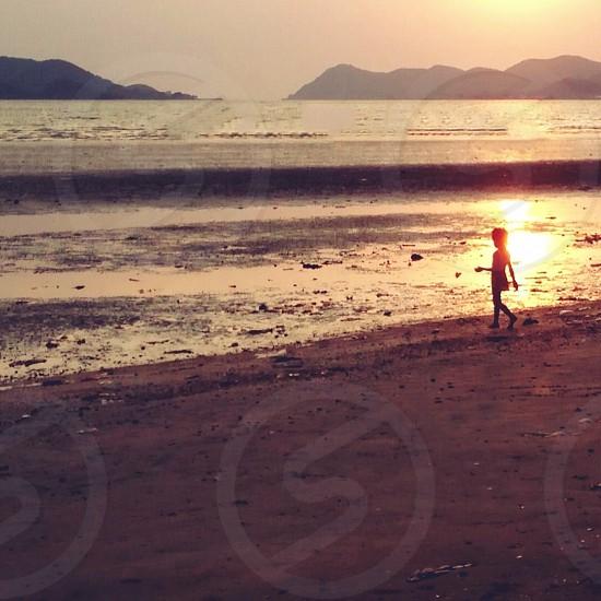 child standing on beach near ocean at sunset  photo