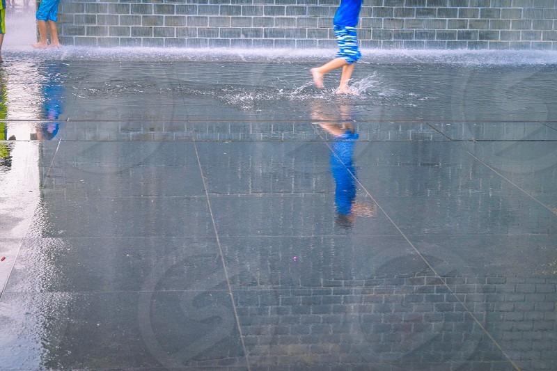 photo of toddler wearing blue shirt teal and white shorts playing on floor full of water during daytime photo