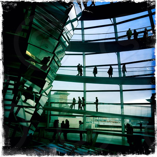 people on floor walking in blue glass building view photo