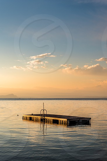 concrete platform on body of vast water under clouds and blue sky photo