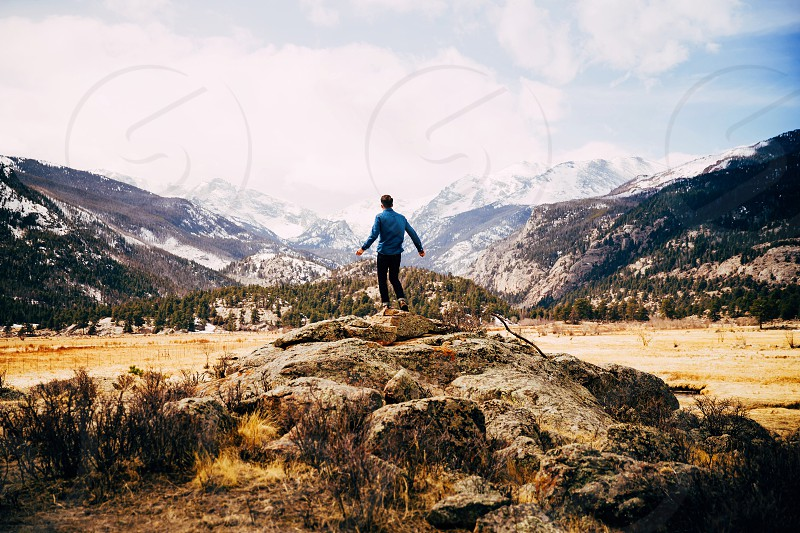 man in blue long sleeve shirt standing on rock formations on barren terrains with mountains along horizon photo