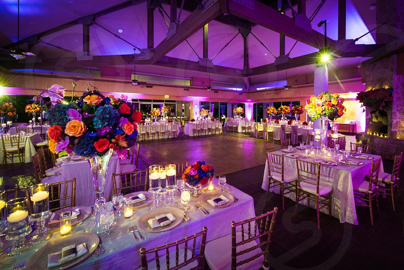 Wedding reception hall with set tables floral arrangements and lighting photo