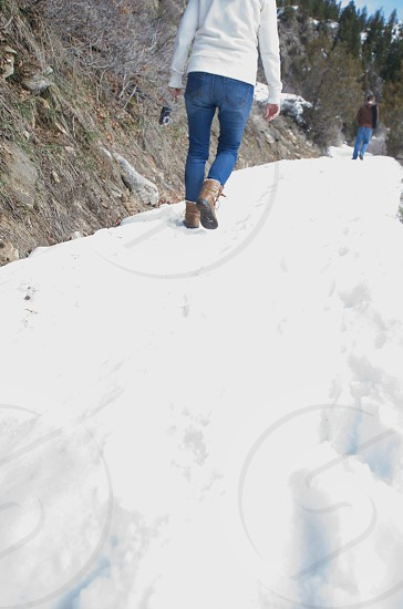 woman in blue denim jeans walking on a snow covered ground photo