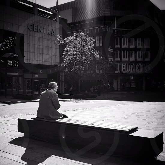 Who is he waiting for...? Alone thinking waiting bench old man city Västerås Sweden photo