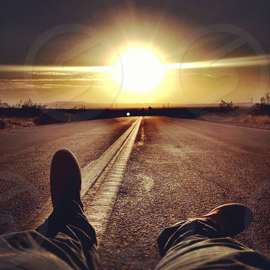person sitting on the center of the road facing sun photo