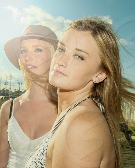 two women with blond hair posing for camera shot during daytime with cloudy sky photo
