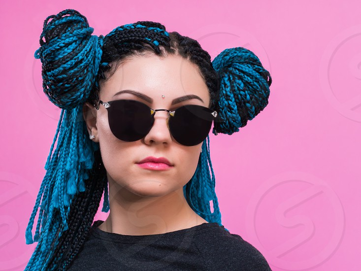 Close-up of woman with blue pigtails braided head African girl with blue braids hairstyle. Hipster portrait girl with sunglasses on colorful background. Lifestyle concept. photo