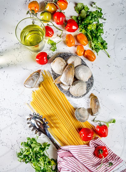 Ingredients for cooking Spaghetti with seafood. Shells musselsa clams vongole tomatoes and white wine photo