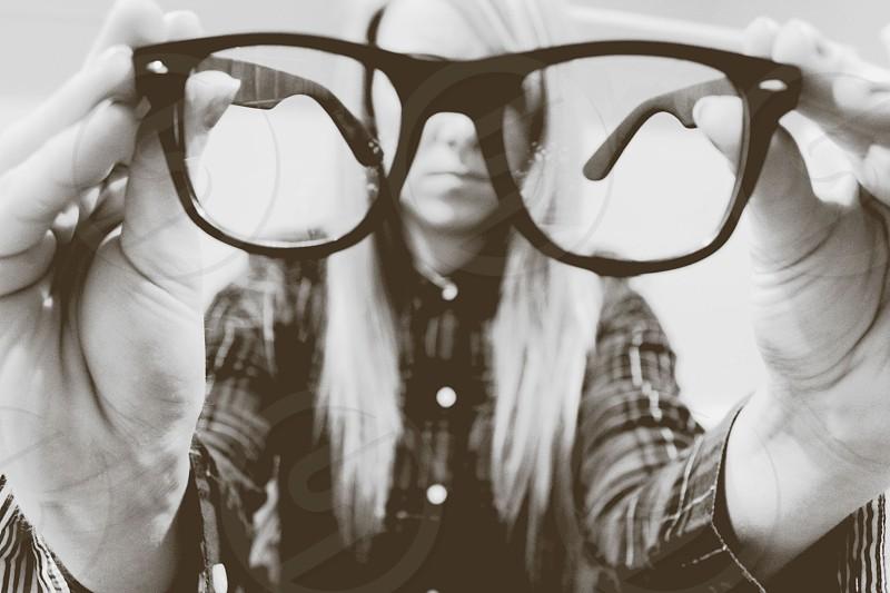 woman holding black framed eyeglasses photo