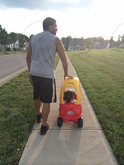 man in grey tank top walking beside girl riding in yellow and red cart photo