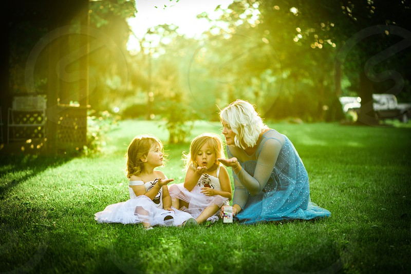 Grandmother kneeling in the grass with her grand daughters.  photo