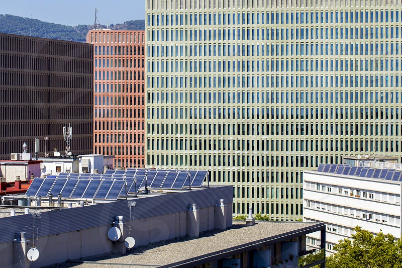 New residential buildings in Spain with solar panels on the roof to save energy. The facades of modern office buildings are visible behind. photo