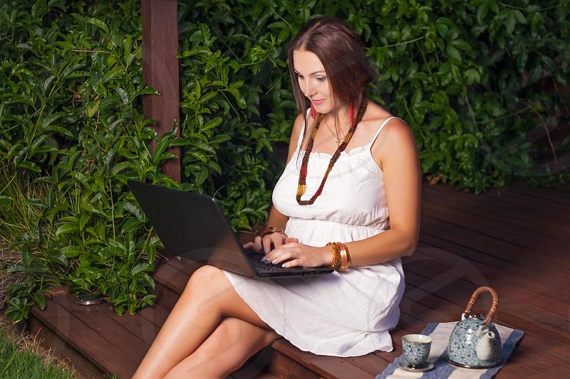 Young woman green wall; plant boho stylenotebook laptop device beauty photo