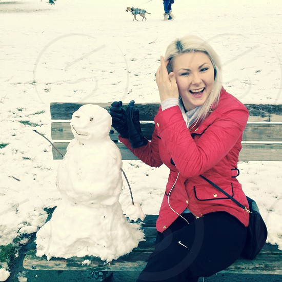 woman sitting on brown wooden bench beside snowman photo
