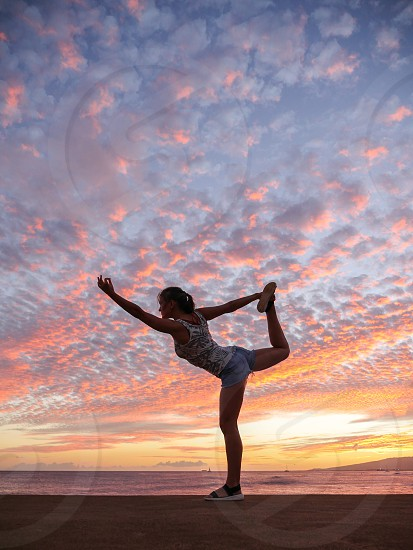 Woman doing a yoga pose at the beach park fitness environment outdoor Hawaii sunset  photo