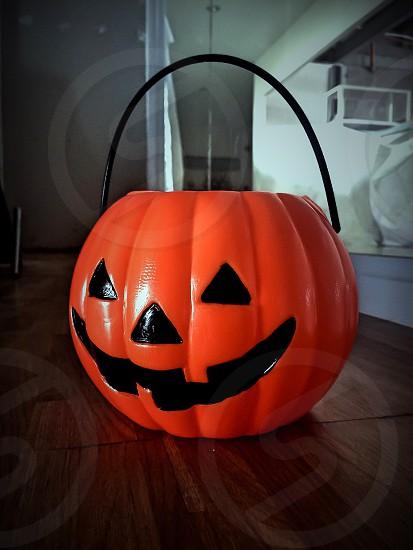 orange and black plastic jack-o-lantern bucket photo