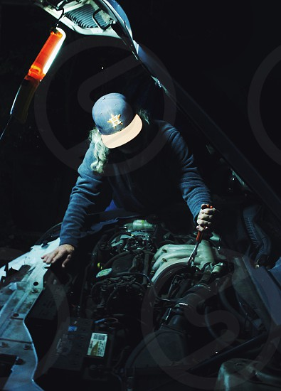 person wearing black sweater fixing car engine photo