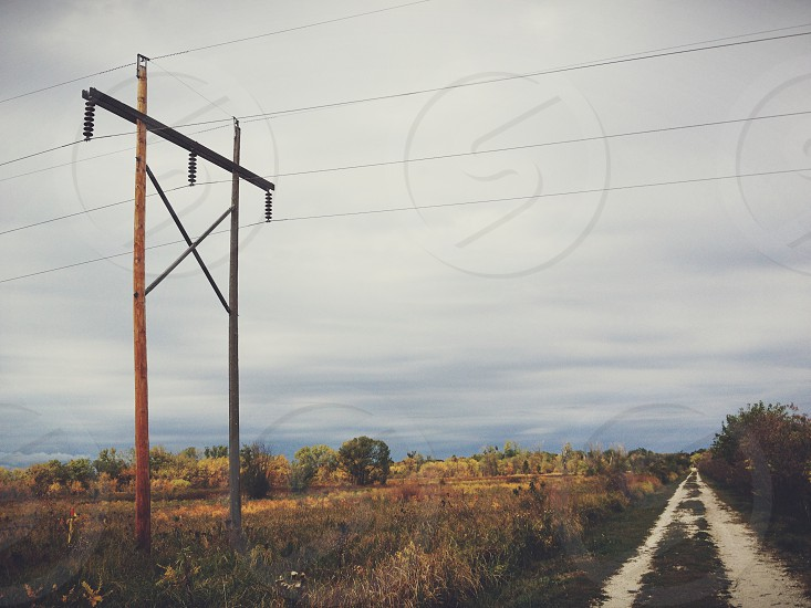 electric posts on brown grass field  photo