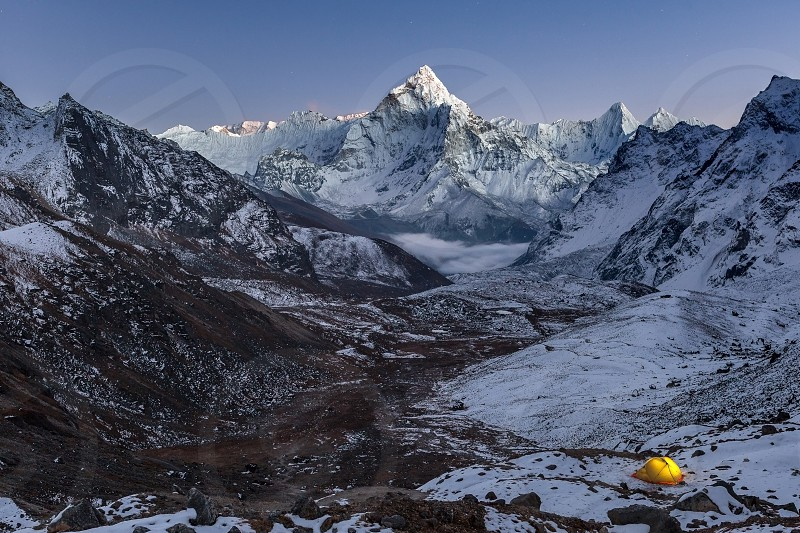 Night camping near amazing Ama Dablam peak in snowy Himalayan mountains Nepal. Extreme mountain camping concept yellow tent lit up by a torch from inside. photo
