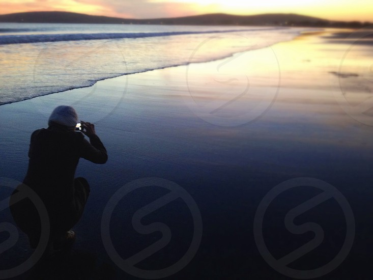 person kneeling on beach holding camera photo