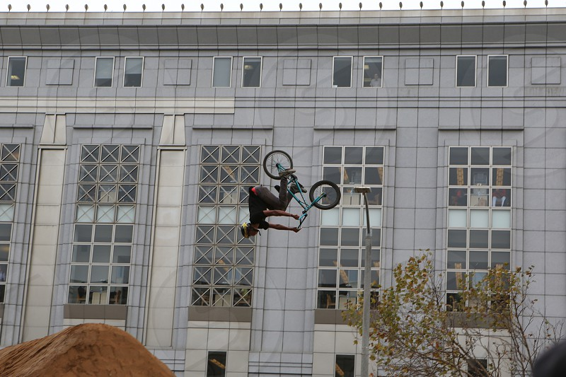 Bicycle daredevil stunts bicycle flips face has been obscured BMX bike competition. photo